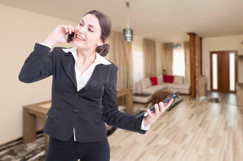 Agente inmobiliario amistoso de la mujer que habla en el teléfono móvil foto de archivo libre de regalías