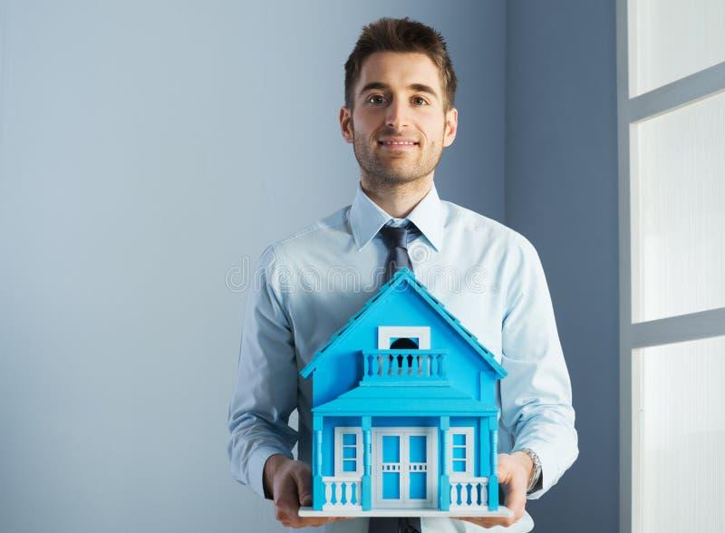 Agente inmobiliario con la casa modelo foto de archivo libre de regalías