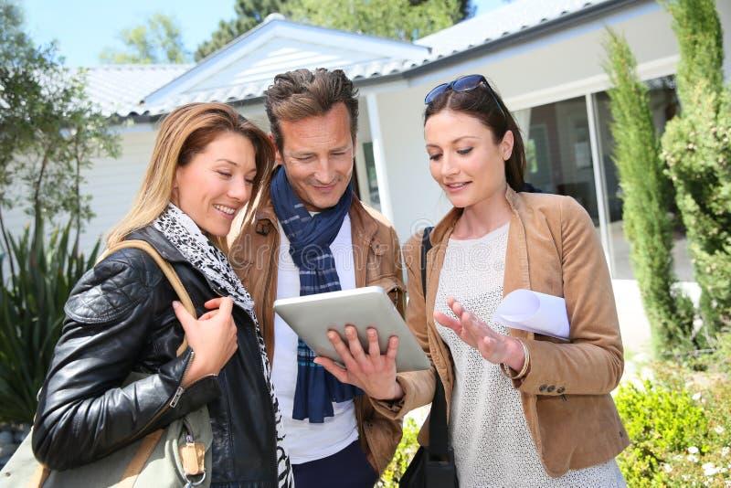 Agente inmobiliario con los clientes delante de su nuevo hogar fotografía de archivo libre de regalías