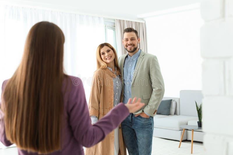 Agente inmobiliario de sexo femenino que muestra la nueva casa para juntarse fotografía de archivo libre de regalías