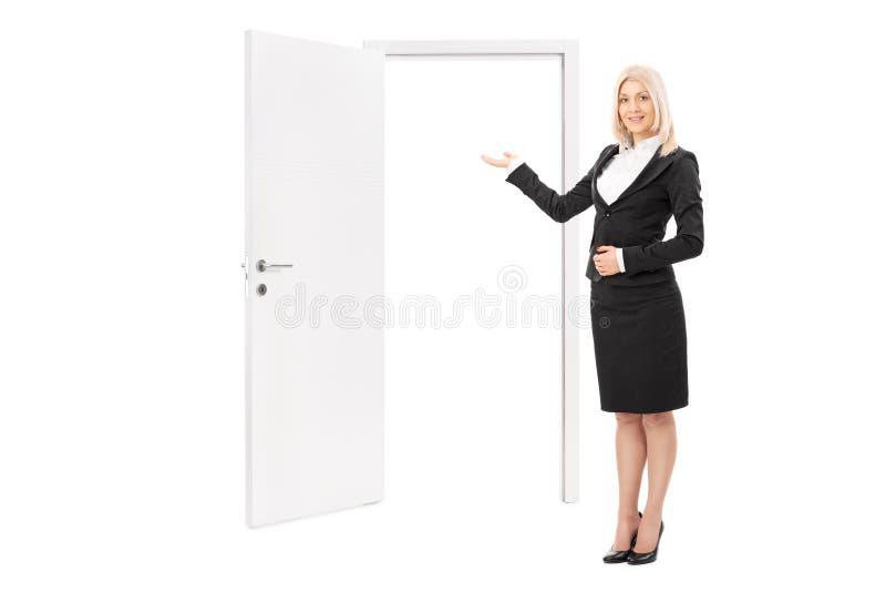 Agente inmobiliario de sexo femenino que señala hacia una puerta imagen de archivo libre de regalías