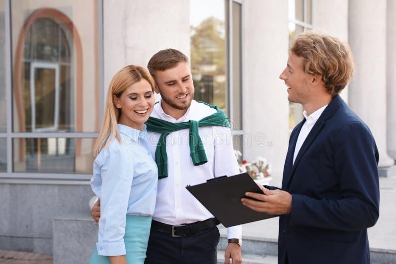 Agente inmobiliario de sexo masculino con los clientes fotografía de archivo