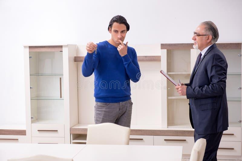 Agente inmobiliario de sexo masculino y cliente masculino en el apartamento fotos de archivo