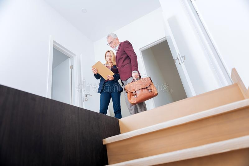 Agente inmobiliario elegante experimentado que muestra su plan rico del apartamento del cliente fotografía de archivo libre de regalías