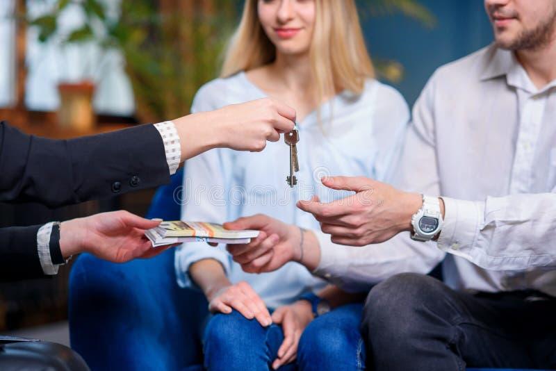 Agente inmobiliario femenino que da llave del plano, casa a los pares jovenes mientras que cliente masculino que da el dinero fotografía de archivo libre de regalías