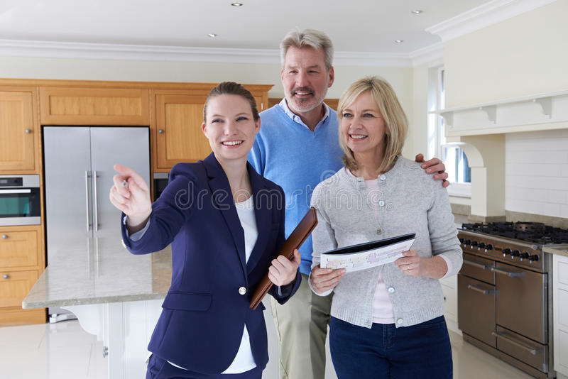 Agente inmobiliario femenino que muestra pares maduros alrededor de casa fotos de archivo libres de regalías