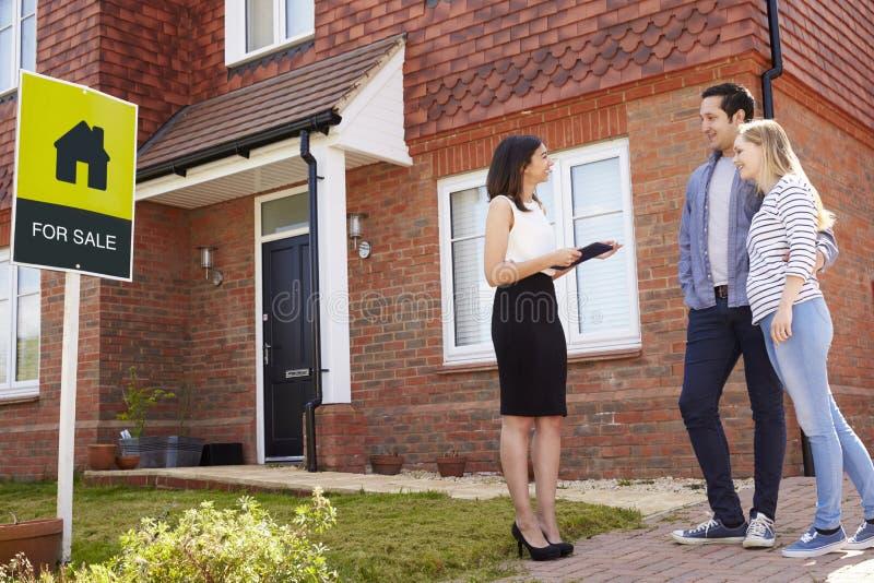Agente inmobiliario fuera de la casa para la venta con los pares jovenes imagen de archivo
