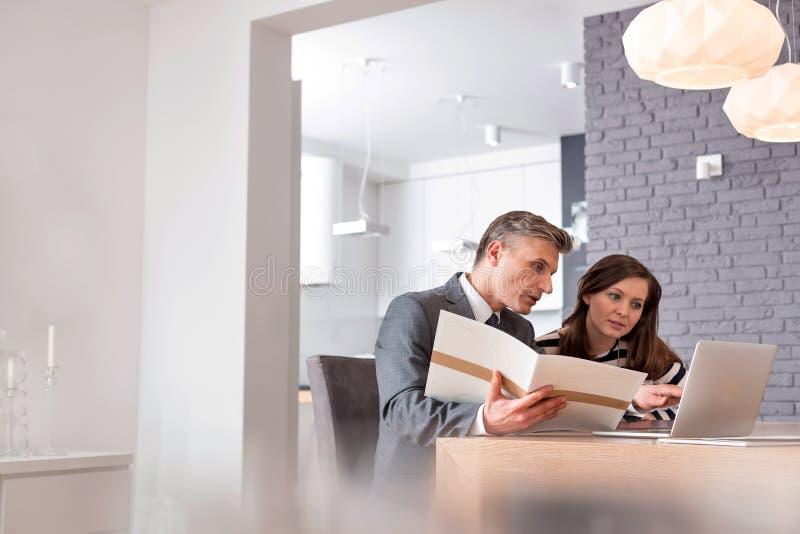 Agente inmobiliario masculino maduro que explica el documento con el ordenador portátil al comprador femenino en la tabla en el a fotos de archivo libres de regalías