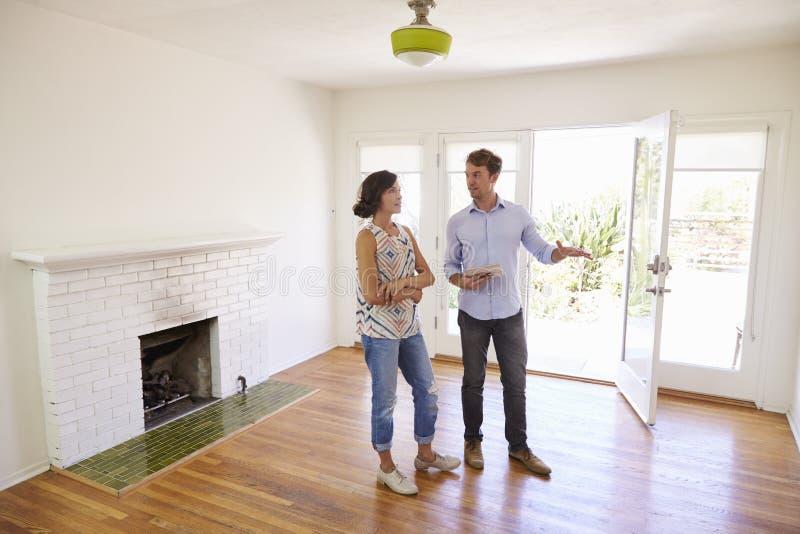 Agente inmobiliario masculino que muestra al cliente femenino alrededor de casa foto de archivo