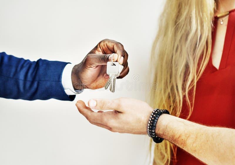 Agente inmobiliario que da la llave de la casa a los clientes imagen de archivo libre de regalías