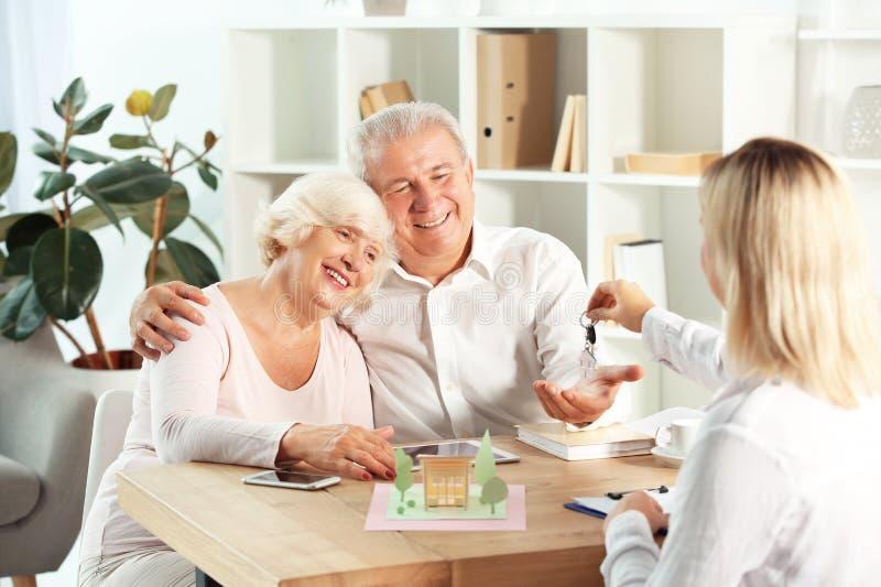 Agente inmobiliario que da llave de la nueva casa a los pares maduros felices en oficina fotos de archivo