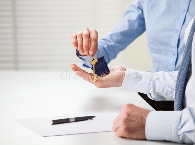 Agente inmobiliario que da llaves al cliente imagenes de archivo