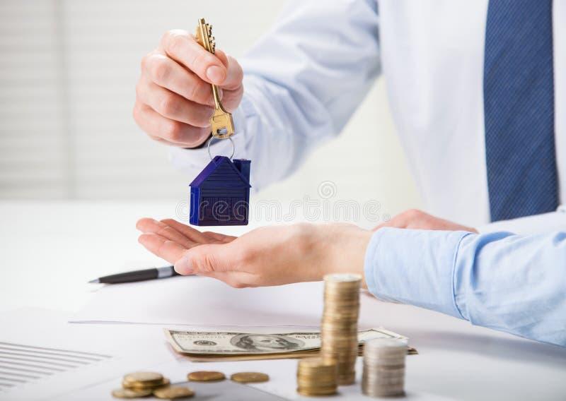 Agente inmobiliario que da llaves al cliente sobre la tabla imagen de archivo libre de regalías