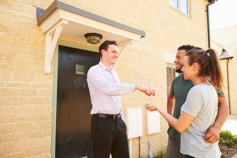 Agente inmobiliario que da llaves de la casa a los nuevos propietarios imágenes de archivo libres de regalías