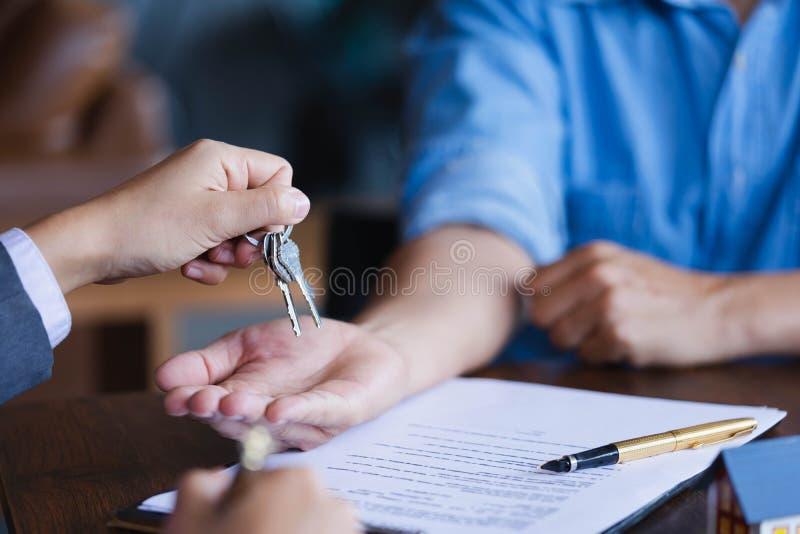 Agente inmobiliario que da llaves a los nuevos propietarios después de signi imagen de archivo