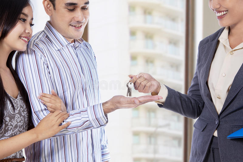 Agente inmobiliario que da una llave fotografía de archivo