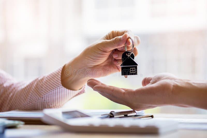 Agente inmobiliario que lleva a cabo llaves de archivaje al cliente después de firmar el contracto de alquiler del arriendo de ac imagen de archivo