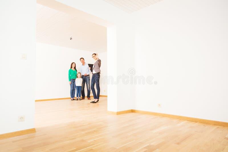 Agente inmobiliario que muestra a clientes un apartamento foto de archivo