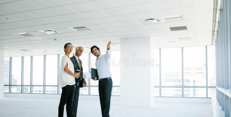 Agente inmobiliario que muestra el nuevo espacio de oficina a los clientes imágenes de archivo libres de regalías