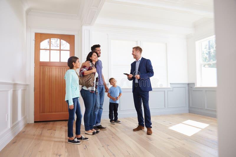 Agente inmobiliario que muestra a la familia hispánica alrededor de nuevo hogar