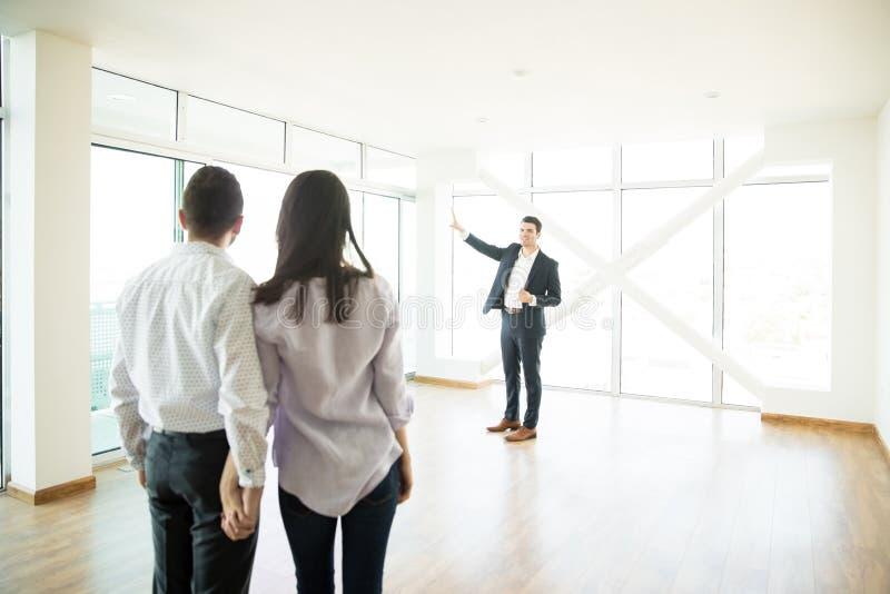 Agente inmobiliario que muestra la nueva casa a los socios cariñosos foto de archivo