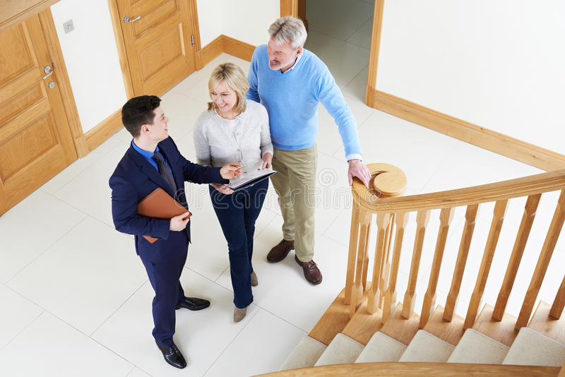 Agente inmobiliario que muestra pares maduros alrededor de la casa para la venta foto de archivo