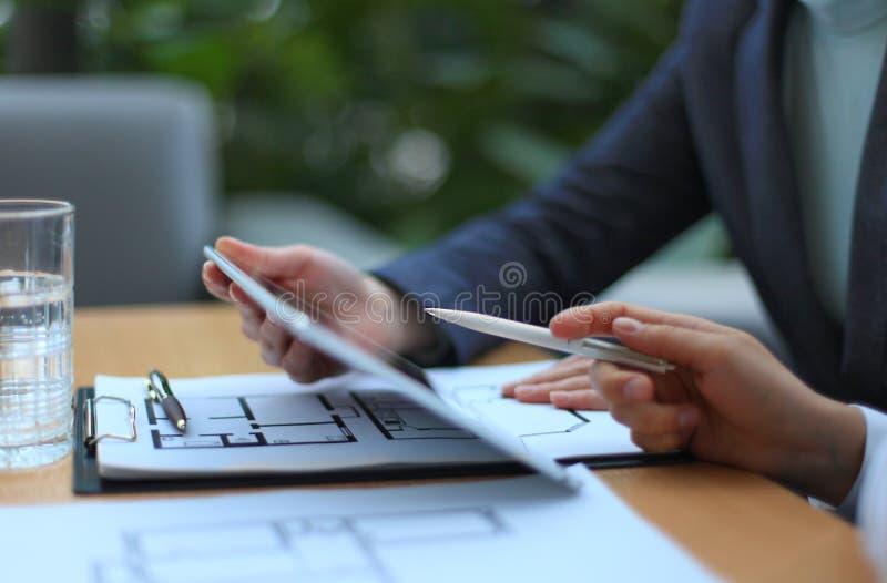 Agente inmobiliario que muestra planes de la casa foto de archivo