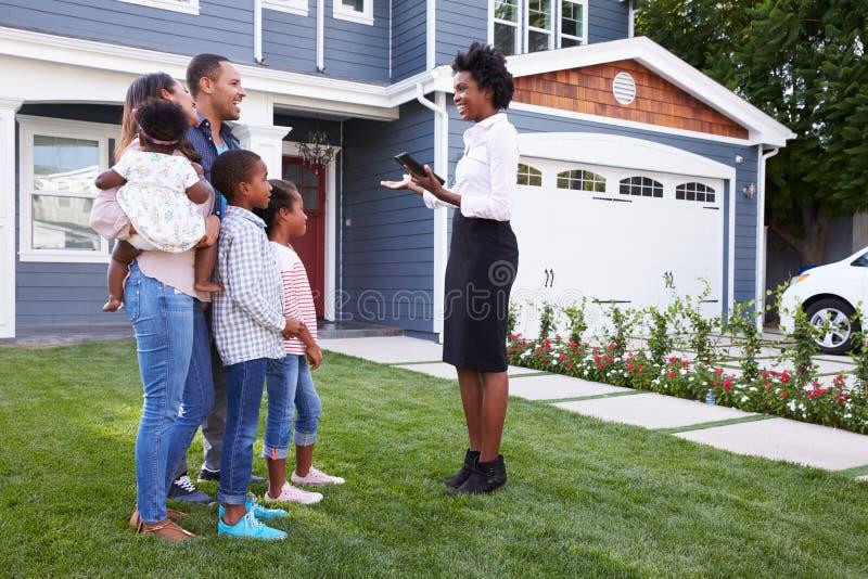 Agente inmobiliario que muestra a una familia una casa fotografía de archivo