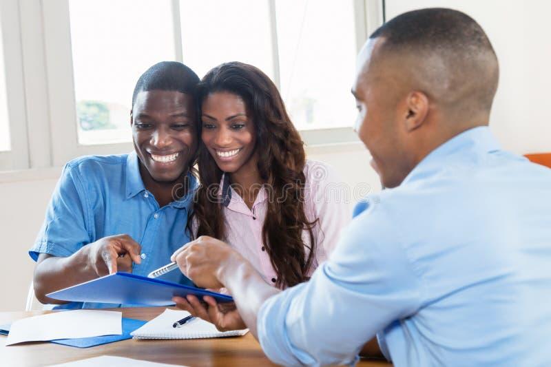 Agente inmobiliario que presenta el contrato a los pares afroamericanos imagen de archivo