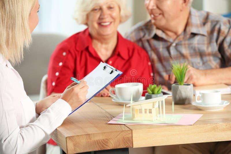 Agente inmobiliario que trabaja con los clientes en oficina imagen de archivo libre de regalías