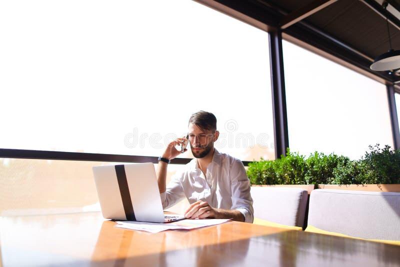 Agente inmobiliario responsable que hojea la nueva información por el ordenador portátil y el calli imágenes de archivo libres de regalías