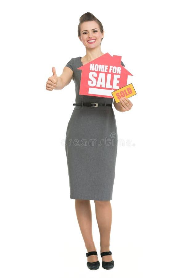 Agente inmobiliario sonriente que muestra los pulgares para arriba y a casa para la sal fotos de archivo libres de regalías