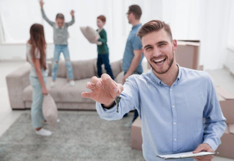 Agente inmobiliario sonriente y situación feliz de la familia en el nuevo apartamento fotos de archivo