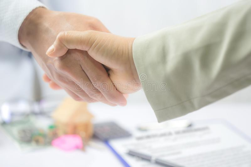 Agente inmobiliario y cliente que sacuden las manos después de firmar un contrato: fotografía de archivo