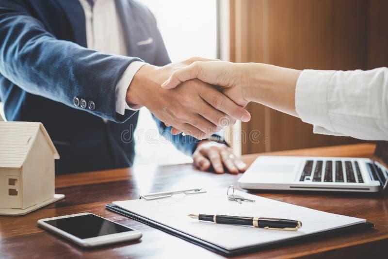 Agente inmobiliario y clientes que sacuden celebrati de las manos junto imagen de archivo