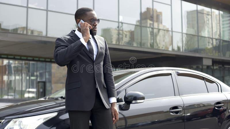 Agente investigativo di servizio segreto che riceve le istruzioni dal telefono, guardia giurata fotografia stock