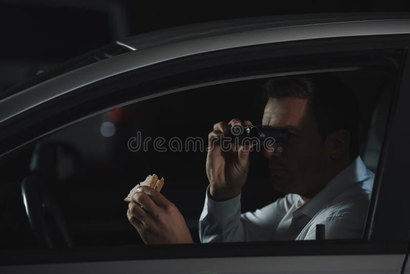agente investigativo privato maschio che fa sorveglianza dal binocolo e che mangia panino fotografia stock