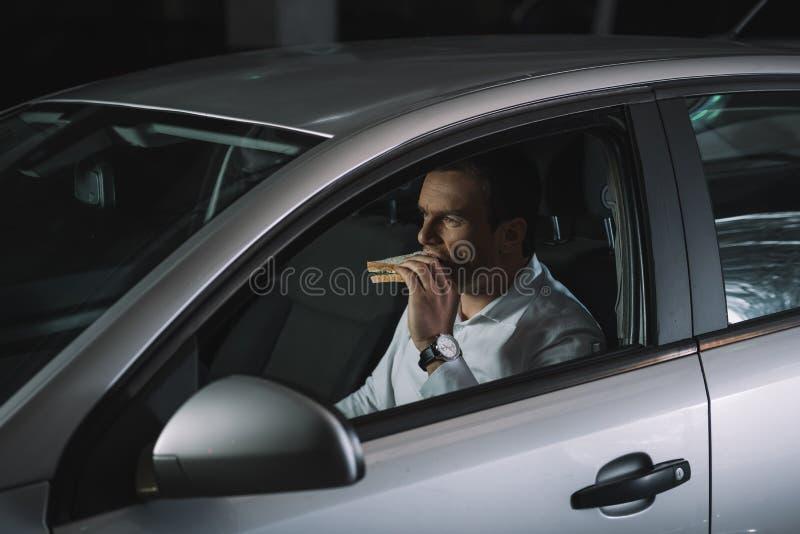 agente investigativo privato maschio che mangia panino immagine stock libera da diritti