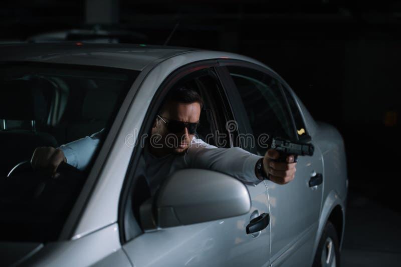 agente investigativo privato maschio in occhiali da sole che tendono dalla pistola immagini stock libere da diritti