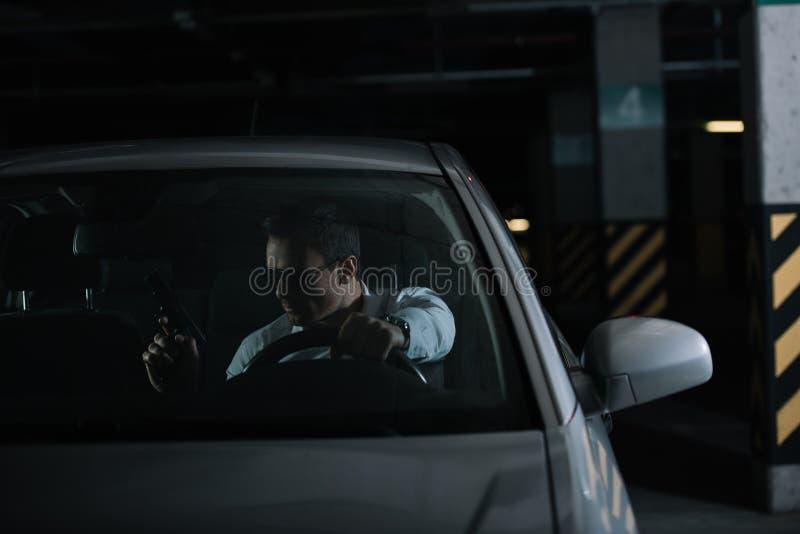 agente investigativo privato maschio serio in occhiali da sole che si siedono in automobile fotografia stock