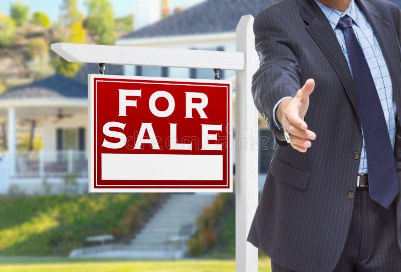 Agente maschio Reaching per la scossa della mano davanti per al segno di vendita immagine stock