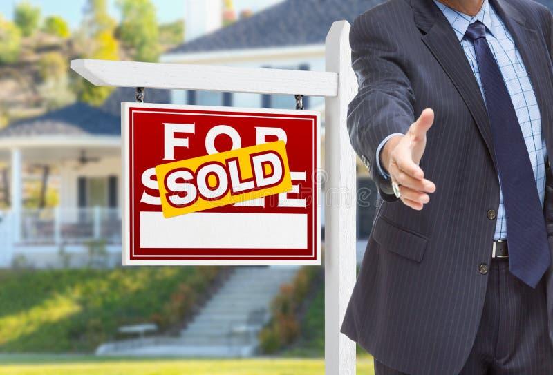 Agente maschio Reaching per la scossa della mano davanti al venduto a per il segno di vendita immagine stock