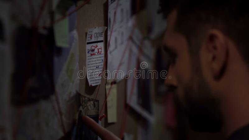 Agente secreto confiado que busca para el criminal en el mapa, encontrando pista fotos de archivo libres de regalías