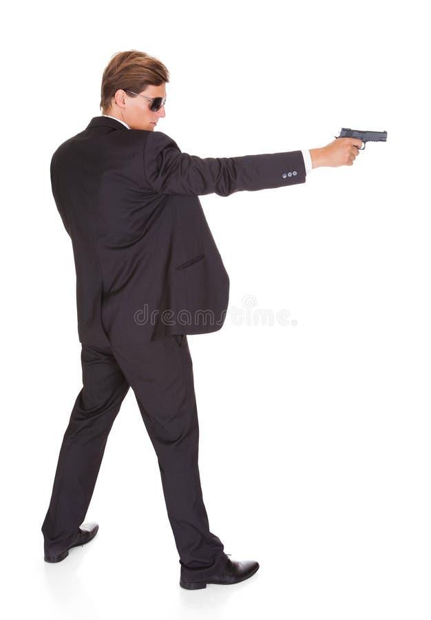 Agente secreto masculino Aiming With Gun imagenes de archivo