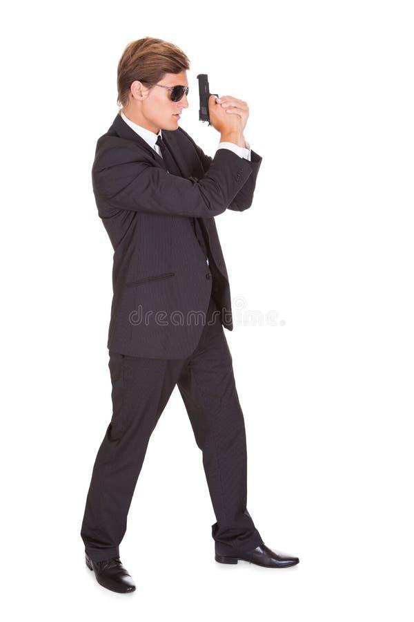 Agente secreto masculino Holding Gun foto de archivo