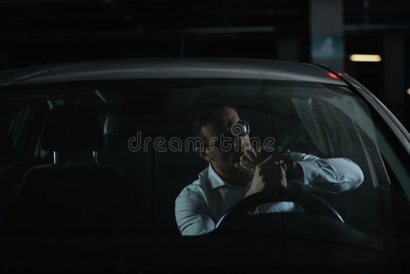 agente secreto masculino sério nos óculos de sol que carregam a arma fotos de stock
