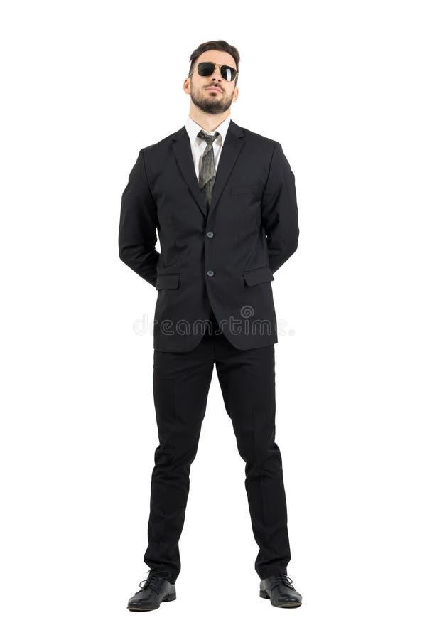 Agente secreto o guardia con las manos detrás de las gafas de sol que llevan traseras imagen de archivo libre de regalías