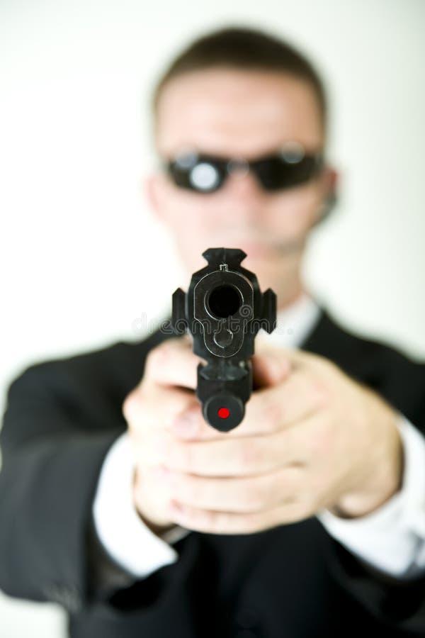 Agente secreto que aponta um injetor imagens de stock