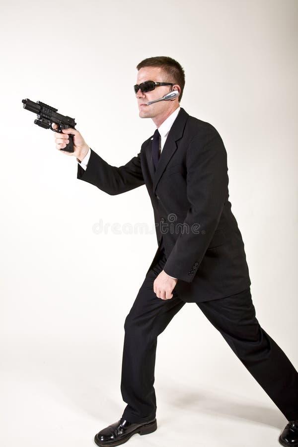 Agente secreto que aponta um injetor fotos de stock royalty free