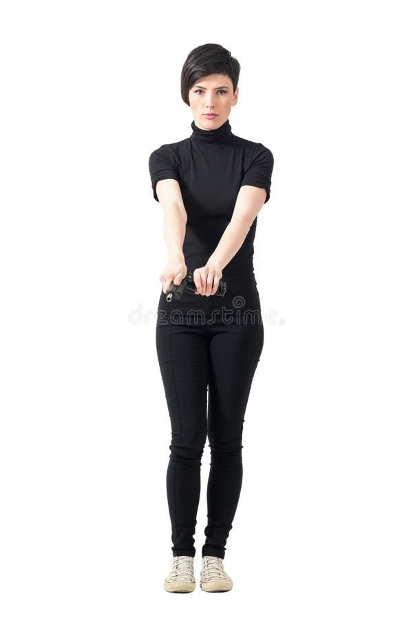 Agente segreto duro della donna in vestiti neri che drizza pistola immagine stock libera da diritti